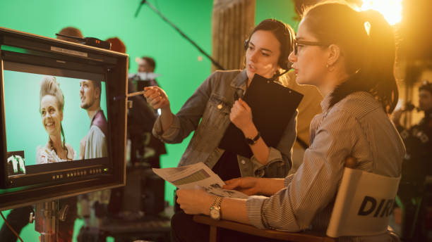 Famous Talented Female Director in Chair Looks at Display talks with Assistant, Shooting Blockbuster. Green Screen Scene in Historical Drama. Film Studio Set Professional Crew Doing High Budget Movie stock photo