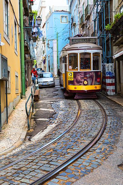 famous tram no 28 on the narrow street of lisbon - eletrico lisboa imagens e fotografias de stock