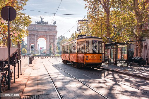 Famous vintage tram in the centre of the Old Town of Milan in the sunny day, Lombardia, Italy. Arch of Peace, or Arco della Pace on the background.