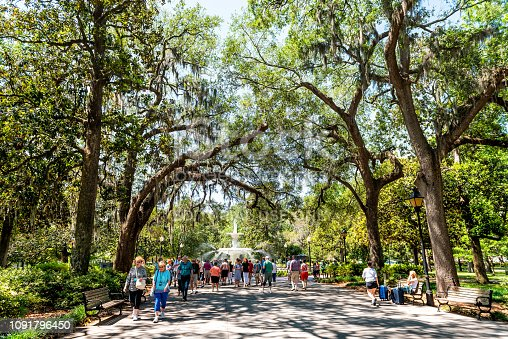 Savannah, USA - May 11, 2018: Famous water fountain in Forsyth park, Georgia during sunny day in summer with people walking on alley street