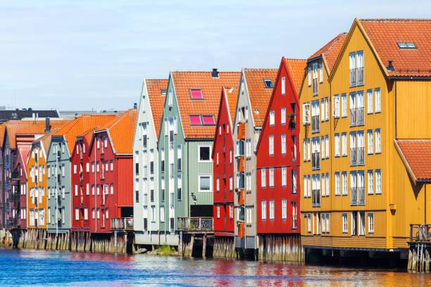 berühmten farbigen holzhäuser in der stadt trondheim, norwegen. bunte häuser auf stelzen und flagge norwegens im sonnigen tag. - norwegen fahne stock-fotos und bilder