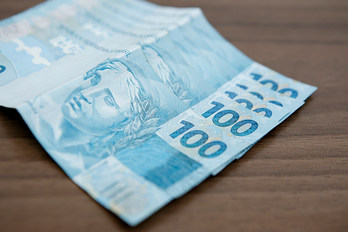A Fan Of 100 Brazilian Bills On A Brown Table Stock Photo - Download Image Now