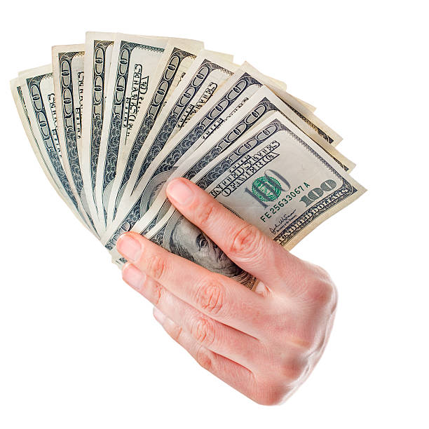 Fan of money dollars in hand isolated on white 100 dollars, caucasian's hand. handful stock pictures, royalty-free photos & images
