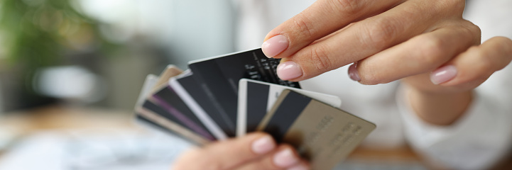 Fan of plastic credit cards is in woman's hand. Bank's favorable offers for consumers concept