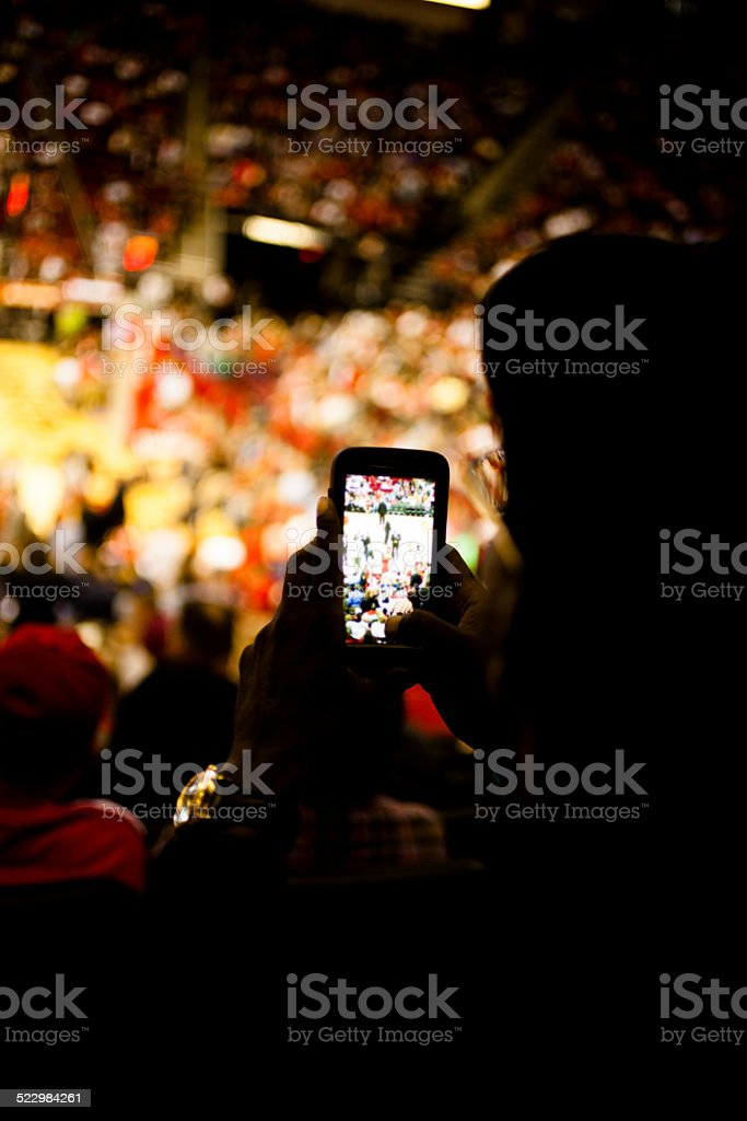 Fan takes photo with cell phone. Sports event. Stadium crowd. stock photo