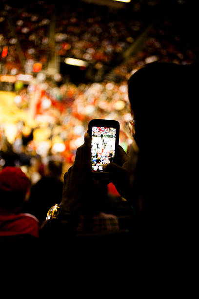 fan takes photo with cell phone. sports event. stadium crowd. - sports event stock photos and pictures