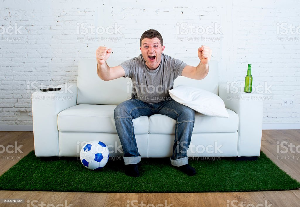 fan watching television in couch grass pitch carpet celebrating goal stock photo