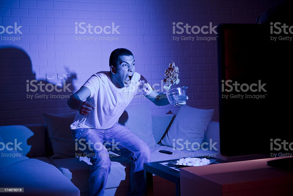 Fan with a beer watching match on TV stock photo
