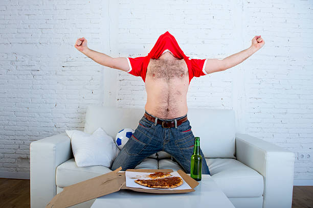 fanatic man with beer watching television football celebrating goal young man watching football game on television celebrating goal crazy with jersey on his head jumping on sofa couch at home with ball holding  beer bottle eating pizza excited football fans stock pictures, royalty-free photos & images