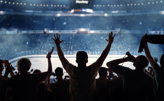 Hockey fans celebrating at a hockey game. We see their silhouettes and fans attributes