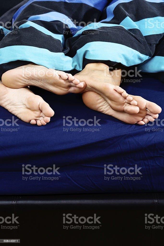 Fancy a bit of fun? Flirtatious feet in bed royalty-free stock photo