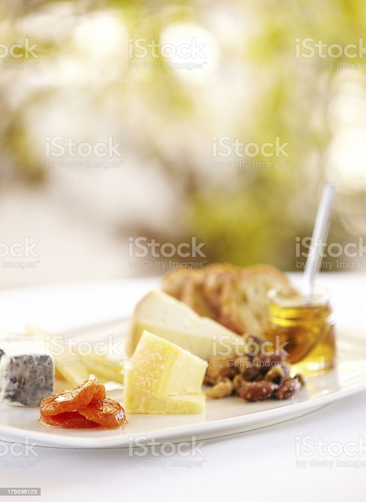 Fancy cheese plate with bread and honey outdoors royalty-free stock photo