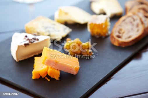 Fancy cheese plate with blue cheese, cheddar, goat cheese, bread, honey and pistachios at a luxury restaurant.  Horizontal shot.
