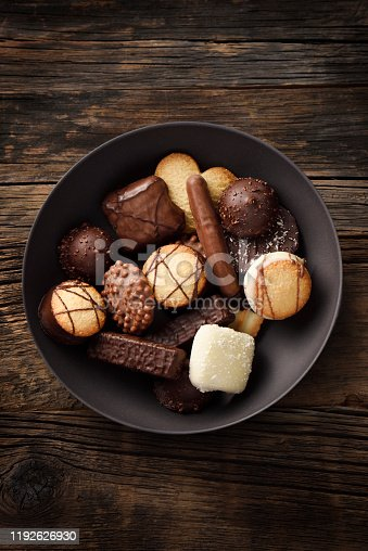 Fancy cookies and chocolates in a black plate on a wooden background