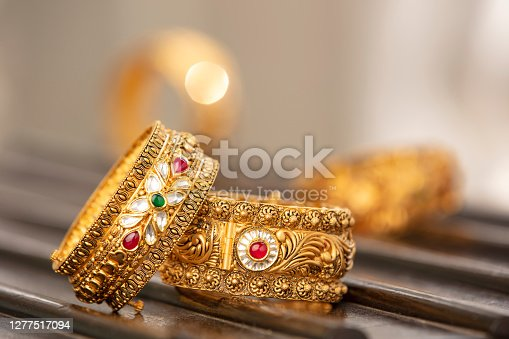 Fancy designer antique golden bracelets for woman fashion studio shot.
