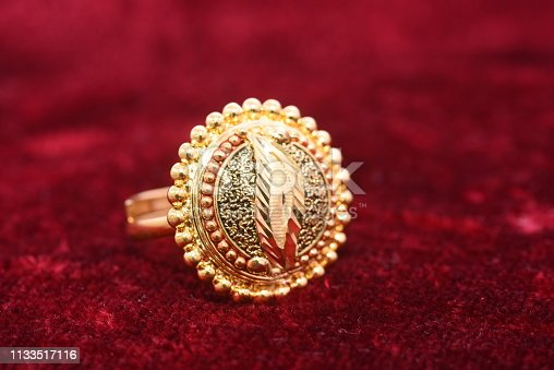 istock Fancy designer precious jewelry golden ring closeup macro image on red background for woman 1133517116