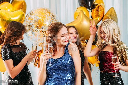 Fancy disco themed home party. Beautiful girls in sequin dresses hanging out, dancing, drinking champagne.