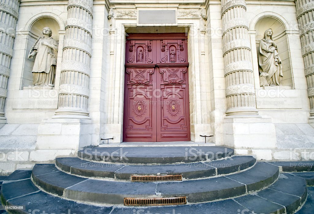 Entrance to French cathedral with statues and carved red door....