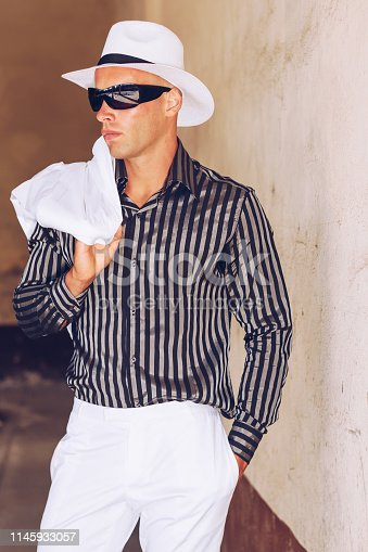 Fancy fashionable man with black sunglasses , white hat  and white summer suit posing.