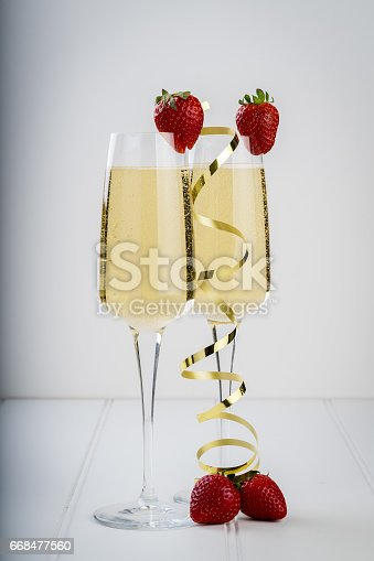 istock fancy glass of bubbly champagne strawberry gold ribbon 668477560