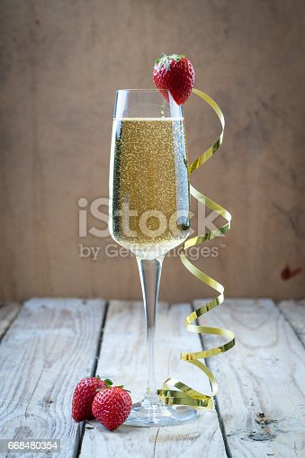 istock fancy glass of bubbly champagne strawberry gold ribbon 668480354