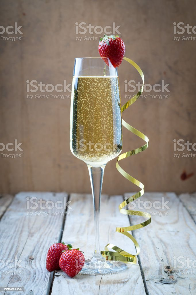 fancy glass of bubbly champagne strawberry gold ribbon stock photo