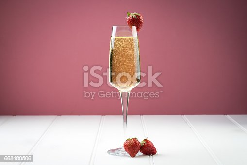 istock fancy glass of bubbly champagne strawberry gold ribbon 668480506