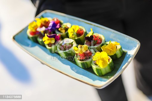 Cucumber serves as a platform for Ahi and Salsa bites decorated with edible flowers. Handheld appetizers served by a waiter at a party.