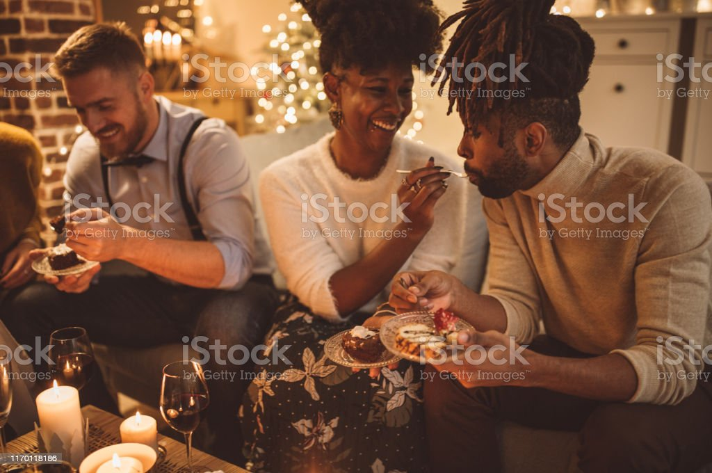 Fancy New Year party Group of friends having a party at home. Sitting on sofa, dressed fancy. Drinking wine, eating cake, talking and laughing. Evening. 25-29 Years Stock Photo