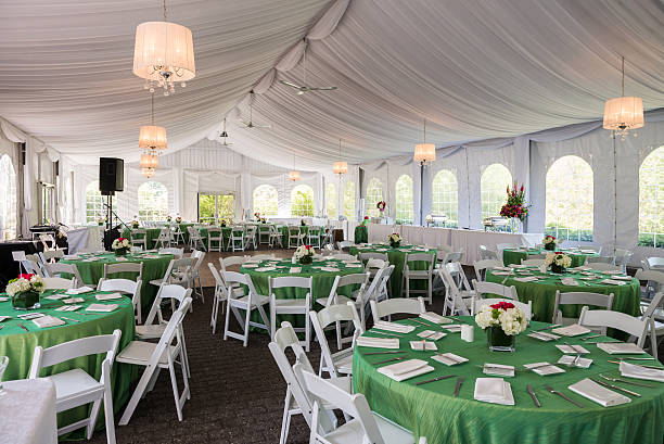 Fancy Outdoor Party Tent The inside of a fancy outdoor party tent prepared with sheer fabric draped ceilings, round guest tables, folding chairs, table cloths, centerpieces and flowers for a birthday party. tent stock pictures, royalty-free photos & images