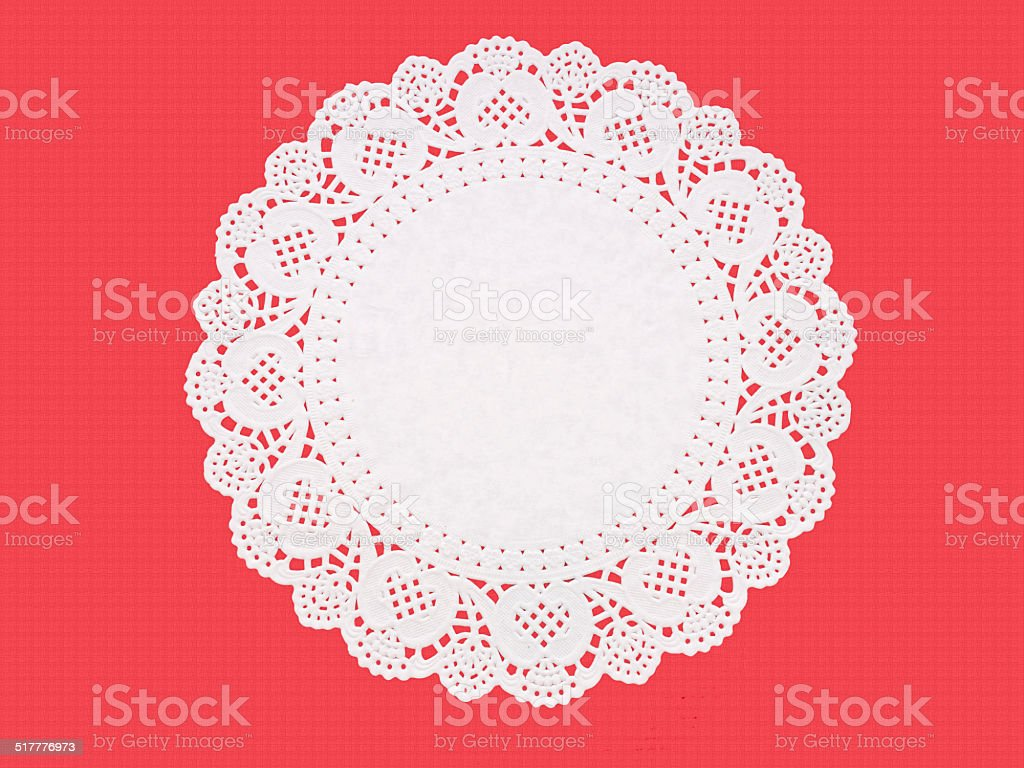Fancy paper doily, round, perforated and embossed, on red stock photo