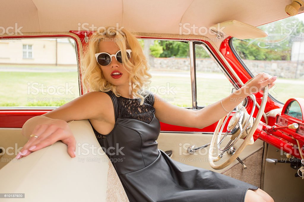 Fancy woman driving a retro car