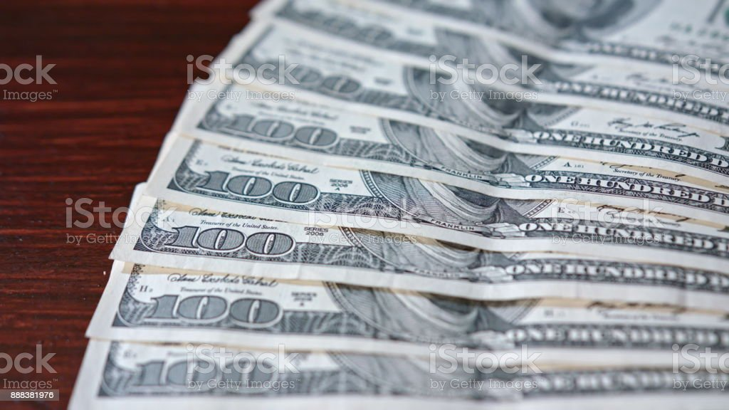 Fanned Pile of Hundred Dollar Banknotes on a Table stock photo
