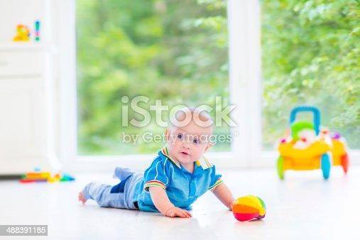 istock Fanny baby with toy in sunny nursery next big window 488391185