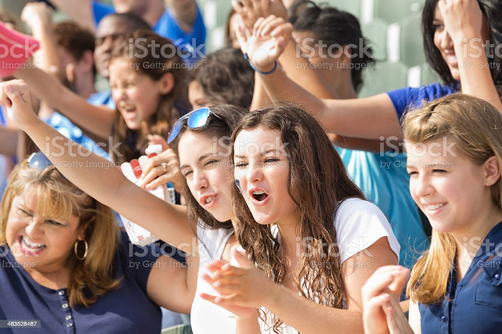 Fans at professional sporting event cheering in stands royalty-free stock photo