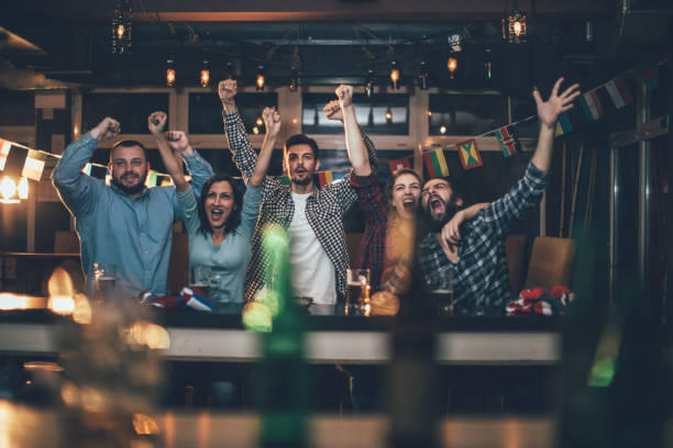 Fans at the bar celebrating together stock photo