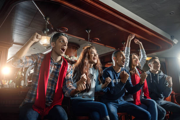 Fans at the bar joyfully screaming and celebrate victory of their favorite sports team stock photo