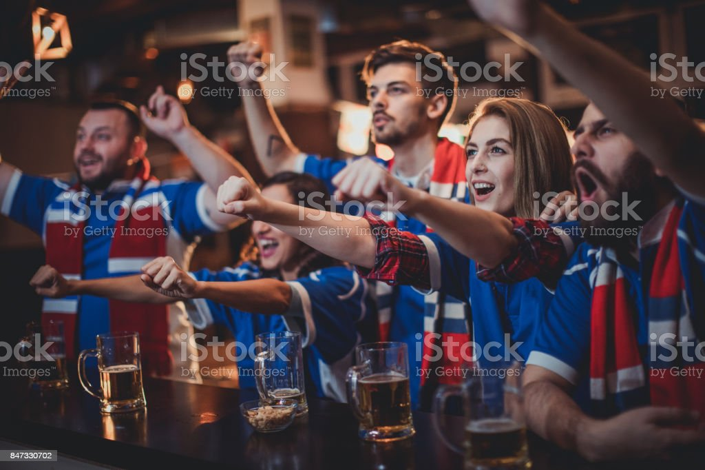 Fans celebrating at the bar stock photo