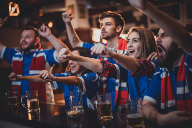 fans celebrating at the bar - sports championship stock photos and pictures