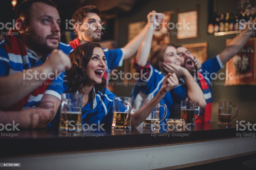 Fans cheering at the bar stock photo