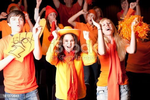 A waist up image of a group of real children and teenagers cheering enthusiastically at a sports event.  Team Color Orange. Shallow DOF.