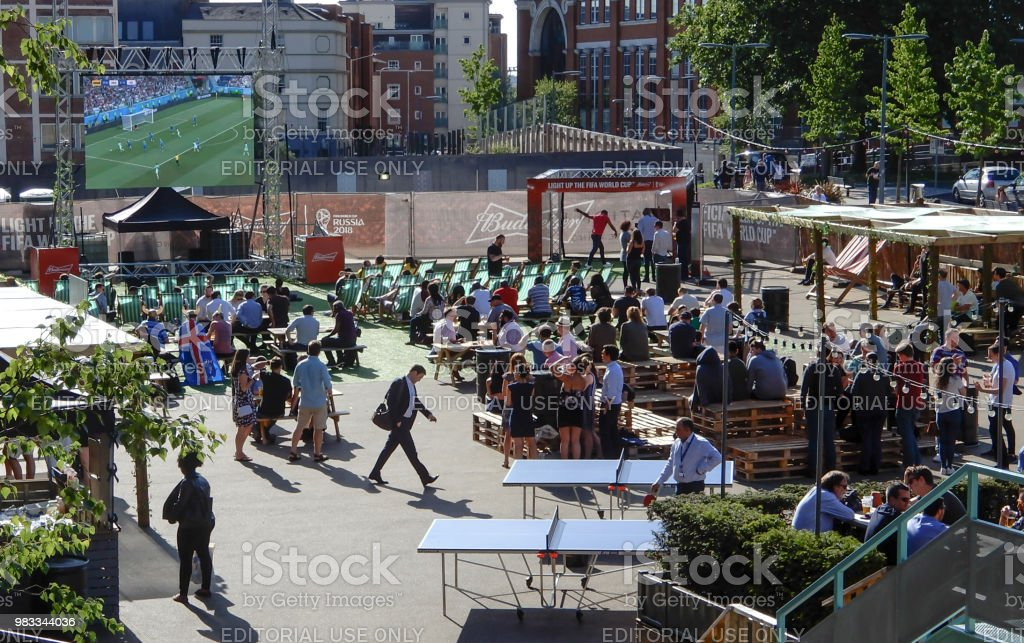 Fans gather at an outdoor bar on Station Hill to watch Nigeria against Iceland in the 2018 Football world cup on a large screen outdoor television stock photo