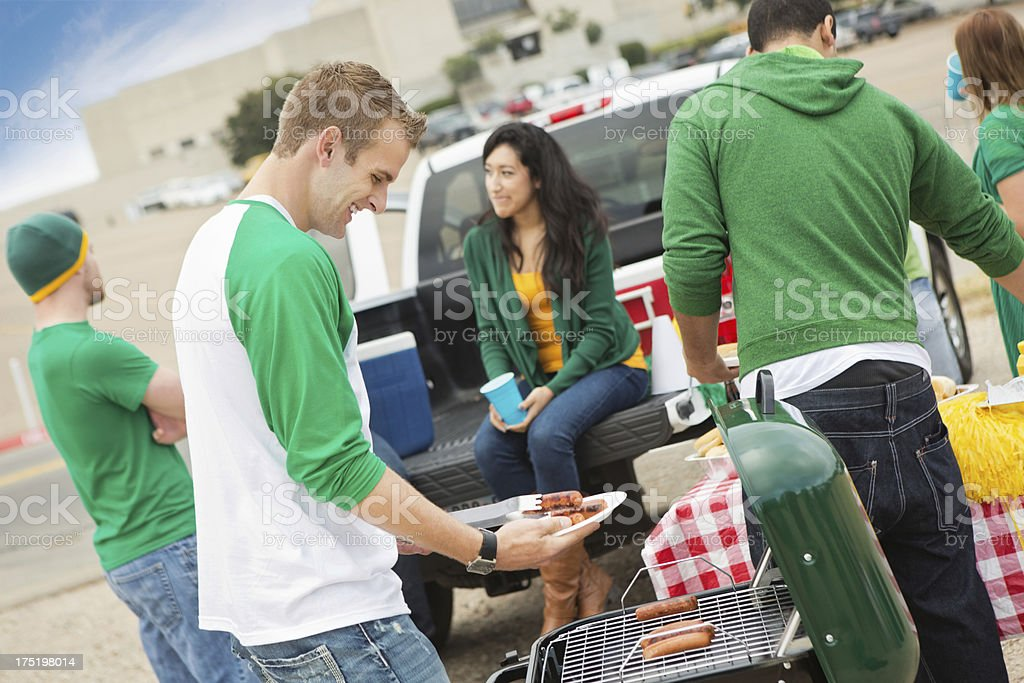 Fans having tailgate cook out at college football stadium stock photo