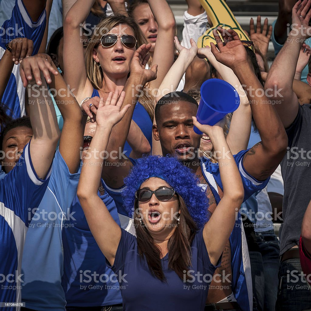 Fans in blue with raised arms cheering for their team royalty-free stock photo