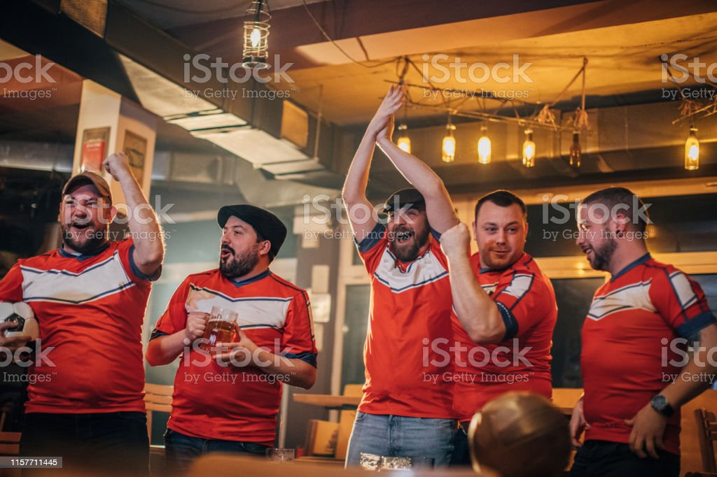 Group of men watching game in sports pub