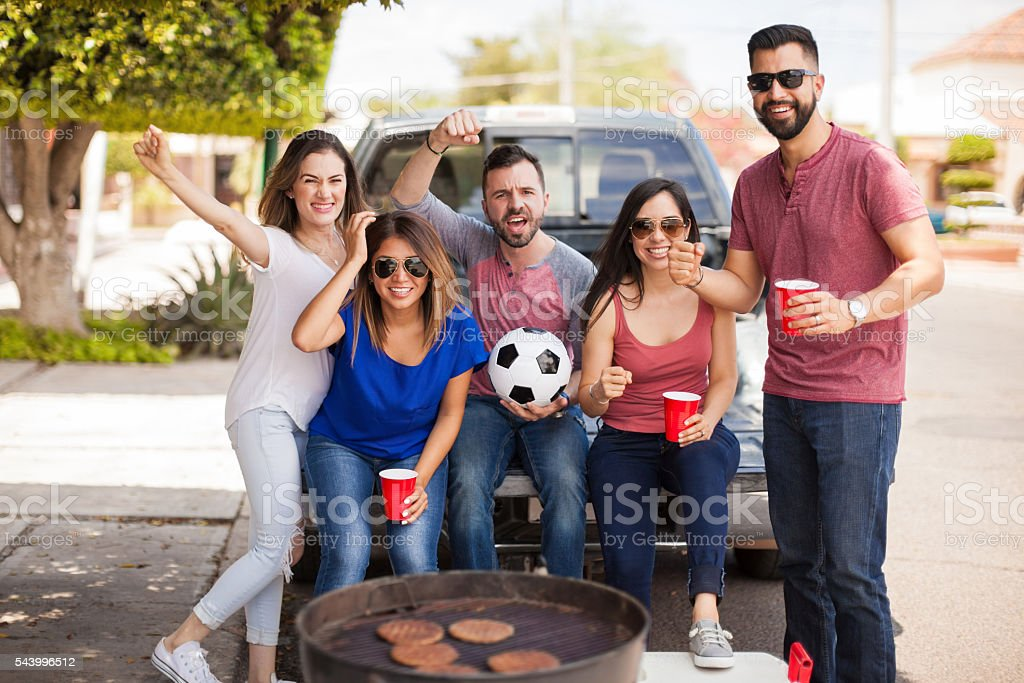 Fans of a soccer team grilling burgers at the game - Photo