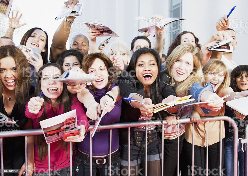 Fans offering notepads for celebrity's signature behind barrier stock photo