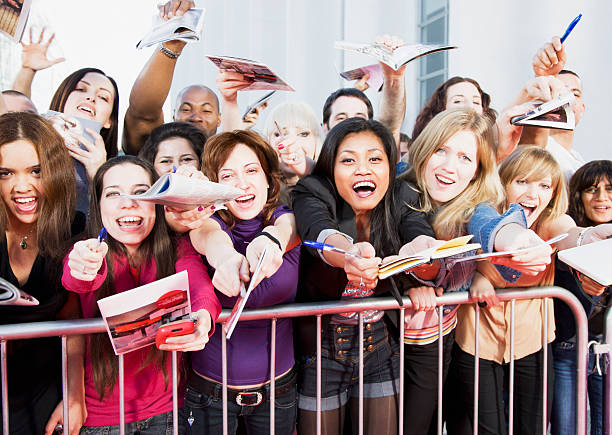 fans offering notepads for celebrity's signature behind barrier - fame stock photos and pictures