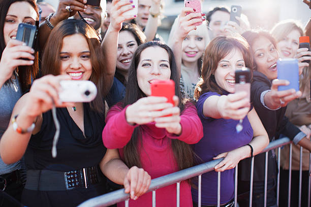 fans taking pictures with cell phone behind barrier - fame stock photos and pictures