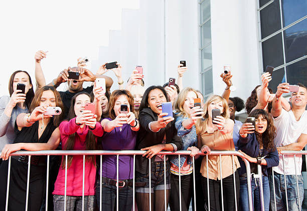 Fans taking pictures with cell phones behind barrier picture id130406861?b=1&k=6&m=130406861&s=612x612&w=0&h=bviodq7g4stsq6sihkggeywnhc8ipdbii h ndhw7lq=